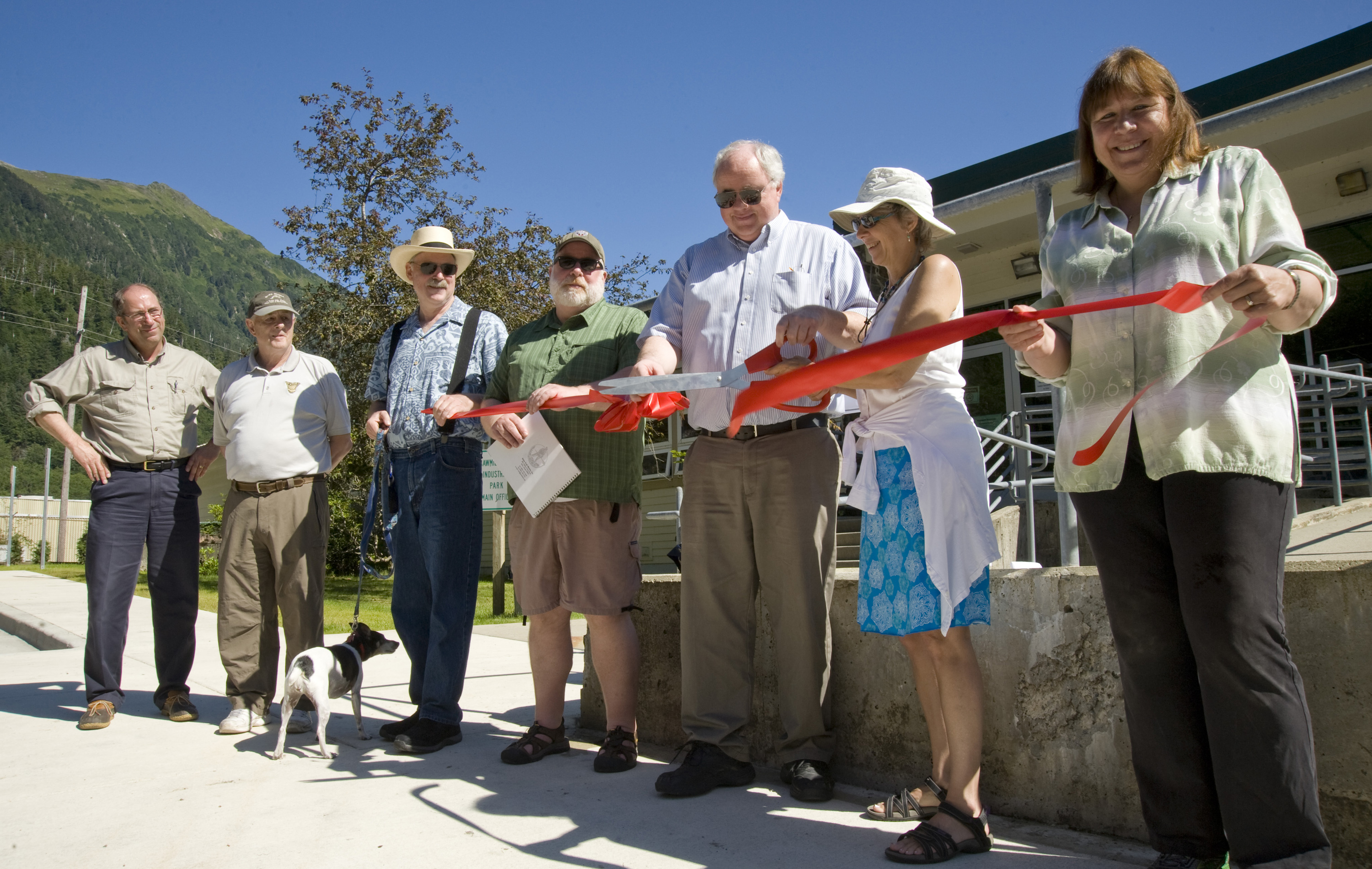 Senator Stedman and his dog Coho participate in the ribbon cutting at the Sawmill Creek Road Completion Celebration.  Pictured from left to right are; DOT&PF Southeast Regional Director Al Clough, Gary Paxton, Senator Stedman, Brian Hanson, DOT&PF Commissioner Pat Kemp, Sitka Mayor Mim McConnell, and Deborah Lyons. (Photo courtesy of James Poulson, Daily Sitka Sentinel)
