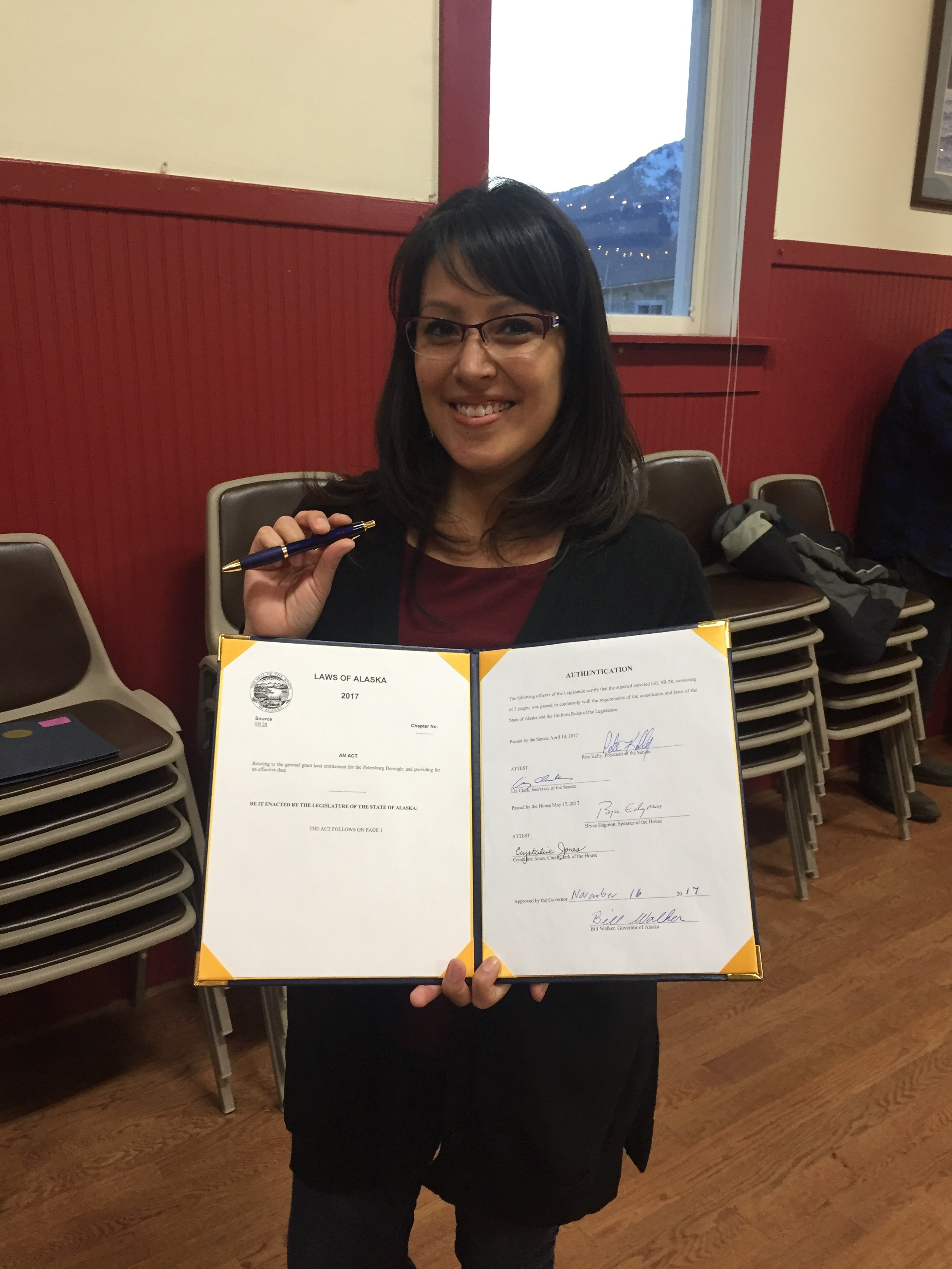 Legislative Aide Melissa Kookesh holding SB 28 and the pen the Governor used to sign it with.